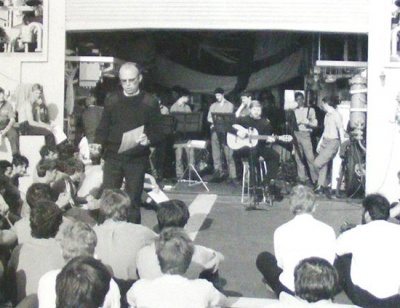 "Passing the time; the Padre conducts a sing-along, with Chris Cole playing guitar, on the flight deck of ""HMS Phoebe"" somewhere in mid Atlantic on their journey to the South Atlantic."