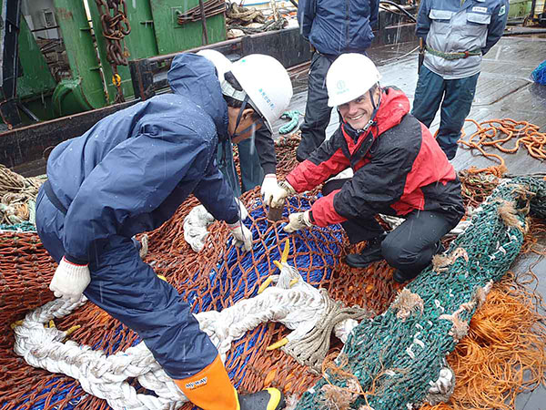Government Officer inspects a fishing net prior to licensing a trawler.